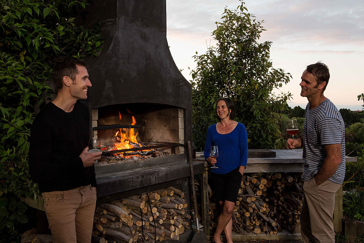 Friends enjoying a relaxing evening with the warmth of a Flare Deluxe outdoor fire and a glass of wine