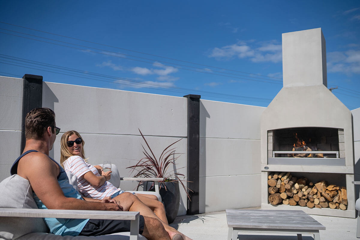 A couple enjoying the warmth of a Flare Deluxe outdoor fire