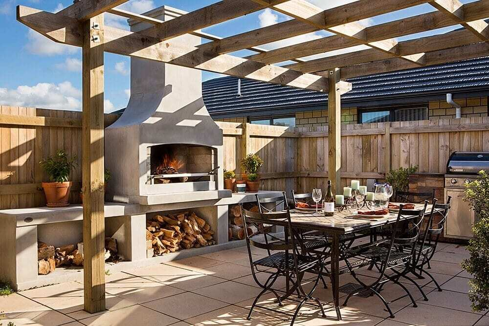 Wood burning senator outdoor fire place brings warmth and beauty to a beautiful dining area.